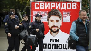 Varias personas pasan junto a un póster electoral del partido nacionalista Rodina (Patria), en Moscú, este jueves.