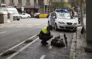 Un agente de la Guardia Urbana atiende a un ciclista accidentado en Consell de Cent con Girona, el pasado noviembre.
