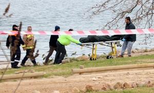 Los servicios funerarios retiran el cadáver hallado este sábado en el embarcadero del río Ebre, en Amposta.