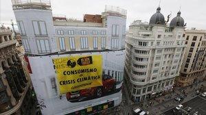 Greenpeace cuelga una pancarta en laGran Vía de Madrid durante el Black Friday.