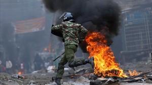 mbenach39656607 an anti riot policeman runs past barricades set on fire by p170812122054