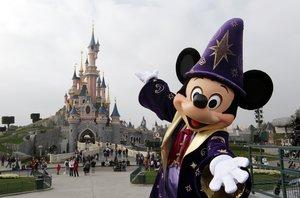 El ratoncito Mickey posa junto a un castillo de Disneyland París.