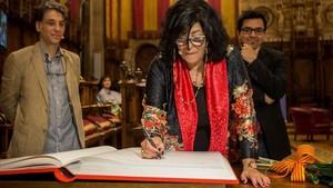 Almudena Grandes, junto al primer teniente de alcalde Gerardo Pisarello, firma en el libro de honor.