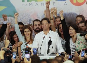 Flanked by his wife Ana Estela left and running mate Manuela d Avila Workers Party presidential candidate Fernando Haddad pauses during his concession speech while his staff and supporters cheer him on in Sao Paulo Brazil Sunday Oct 28 2018 Brazila s Supreme Electoral Tribunal declared far-right congressman Jair Bolsonaro the next president of Latin Americaa s biggest country AP Photo Andre Penner