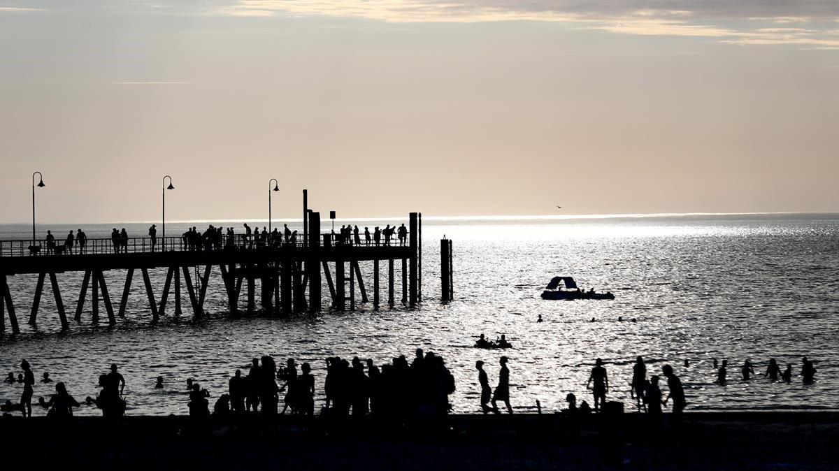 Bañistas en la playa de Gleneig, en Adelaida, al sur de Australia, este miércoles.