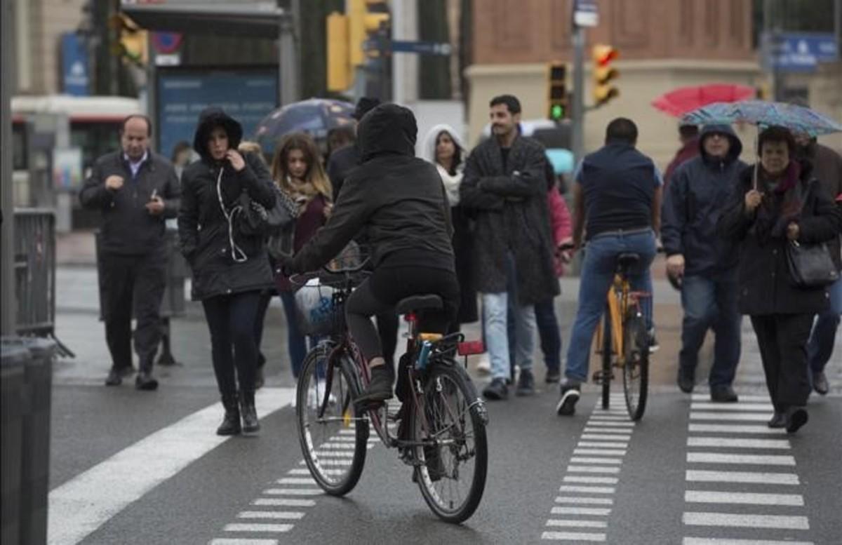 Dos ciclistas intentan cruzar uno de los pasos de peatones de la plaza de Espanya.