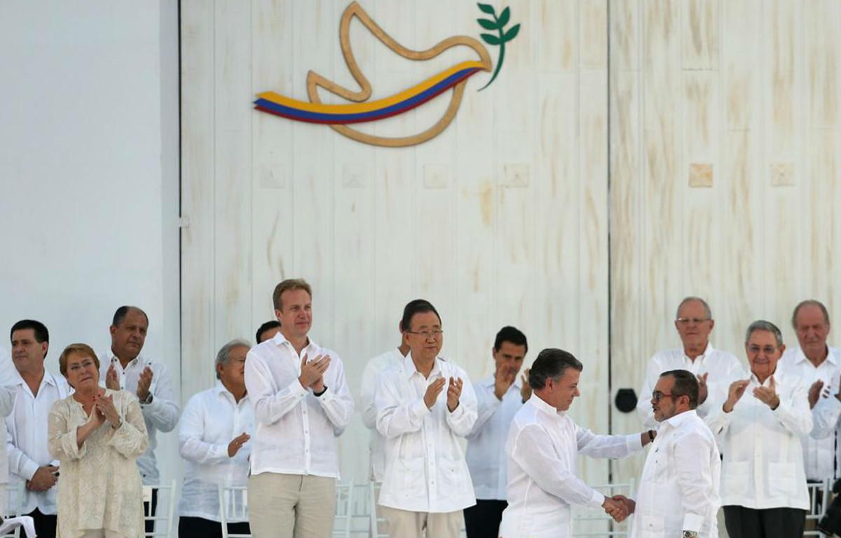 El presidente Santos y el líder guerrillero Timochenko se dan la mano en presencia de invitados de todo el mundo, entre ellos el rey Juan Carlos (primero por la derecha).