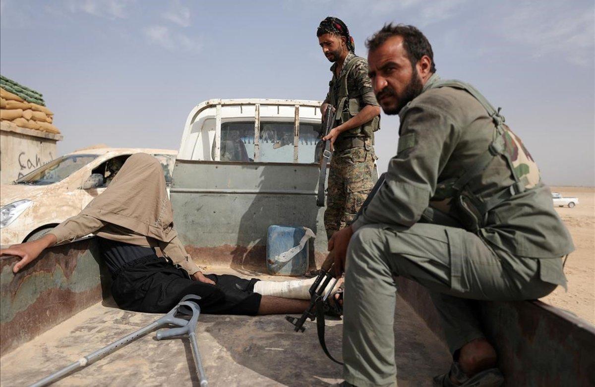 Combatientes de las Fuerzas Democráticas de Siria tras arrestar a un hombre herido durante su combate con el Estado Islámico en la zona norte de Deir al-Zor, en Siria.