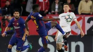 Dembelé y Lenglet pugnan por un balón ante la mirada de Suárez.