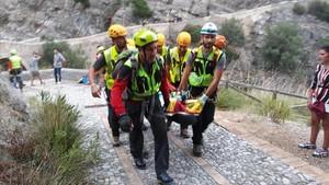 Miembros de los servicios de rescate retiran en camilla a un excursionista afectado por las inundaciones en la Garganta de Raganell.