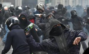 Manifiestantes antisistema lanzan botellas contra la policía italiana en Milán.