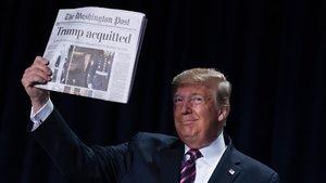 Donald Trump muestra un ejemplar de periódico.