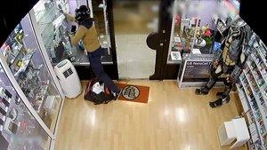 Imágenes captadas por la cámara de seguridad de un momento del robo en una tienda de móviles del Eixample de Barcelona.
