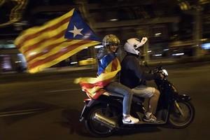 Dos independentistas en moto ondean una 'estelada' el 17 de octubre en Barcelona.