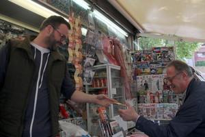 Un hombre compra un billete de la Grossa de Sant Jordi en un quiosco de Barcelona.