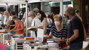 Lectores ante los estands de libros en el paseo de Gràcia de Barcelona, este jueves.