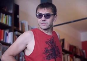 Juan Carlos Monedero con su 'look' playero en una secuencia del vídeo promocional de la Universidad de Verano de Podemos. / PODEMOS.