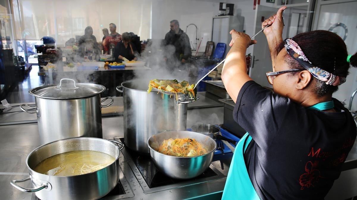 Los voluntarios del comedor social y solidario preparan el menú del día en los fogones de Ca l'Isidret