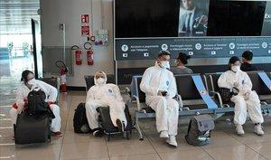 Medidas de protección de un grupo de pasajeros en el aeropuerto romano de Fiumicino.