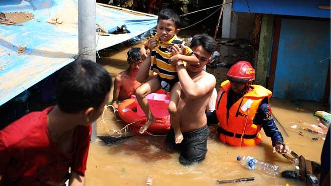 Mueren al menos 16 personas a causa de las inundaciones en Indonesia. En la foto, un rescate en un barrio inundado de Yakarta.
