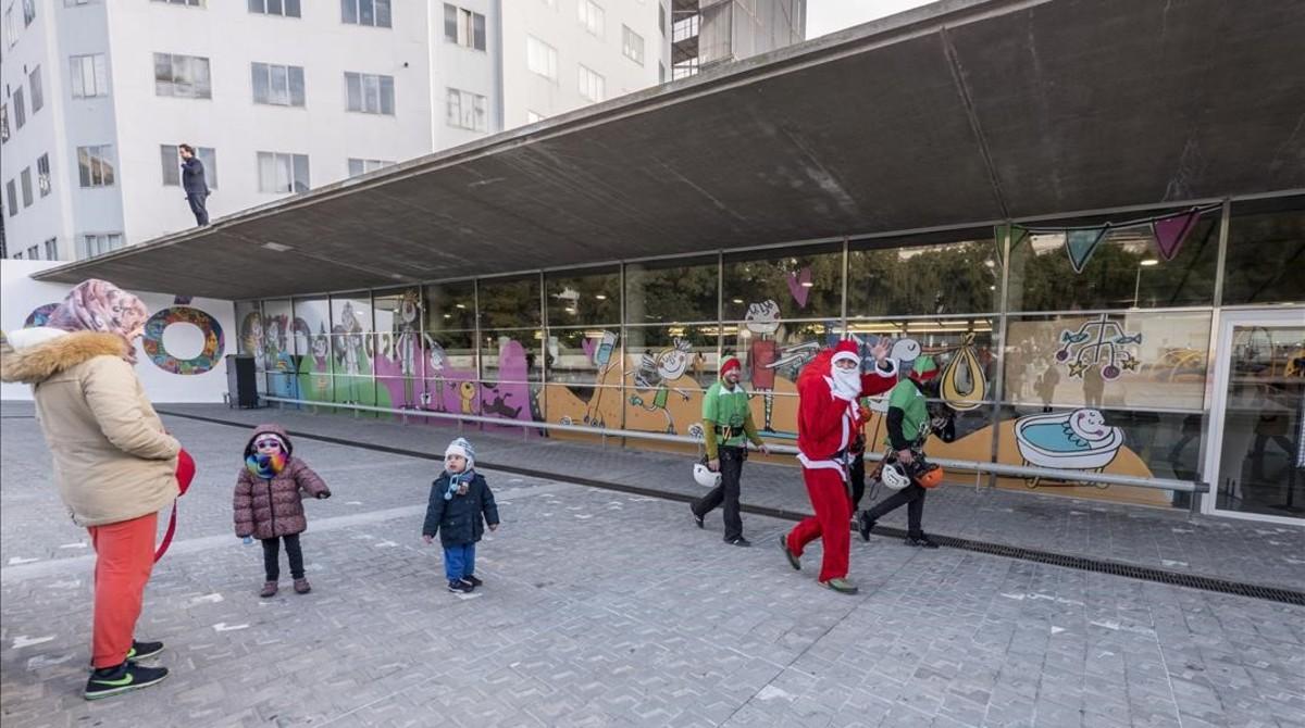 Papa Noel llega al hospital Vall de Hebron haciendo un descenso en rapel desde la planta 15 del hospital Maternoinfantil