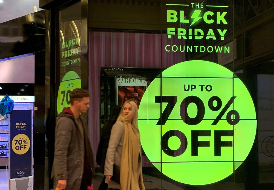 People walk past a sign advertising Black Friday offers at a perfume store in Manchester, Britain November 20 2019. Picture taken November 20, 2019. REUTERS/Phil Noble