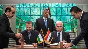 El representante de Fatá, Azam al Ahmad (derecha) y el de Hamás, Saleh al Arouri, firman el acuerdo en El Cairo.