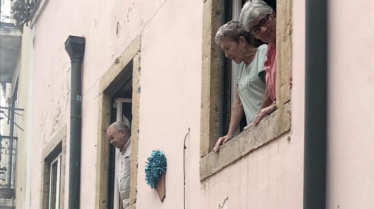 Turistas asomados a la ventanas en la Alfama.