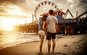 Una pareja en la playa viendo una feria.