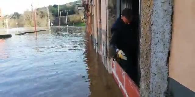 Un vecino tapiando la puerta de su casa, frente a la gasolinera de Pont Major (Girona).