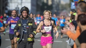 Un bombero y una runner, durante la cursa dels Bombers de Barcelona celebrada en octubre del 2016.