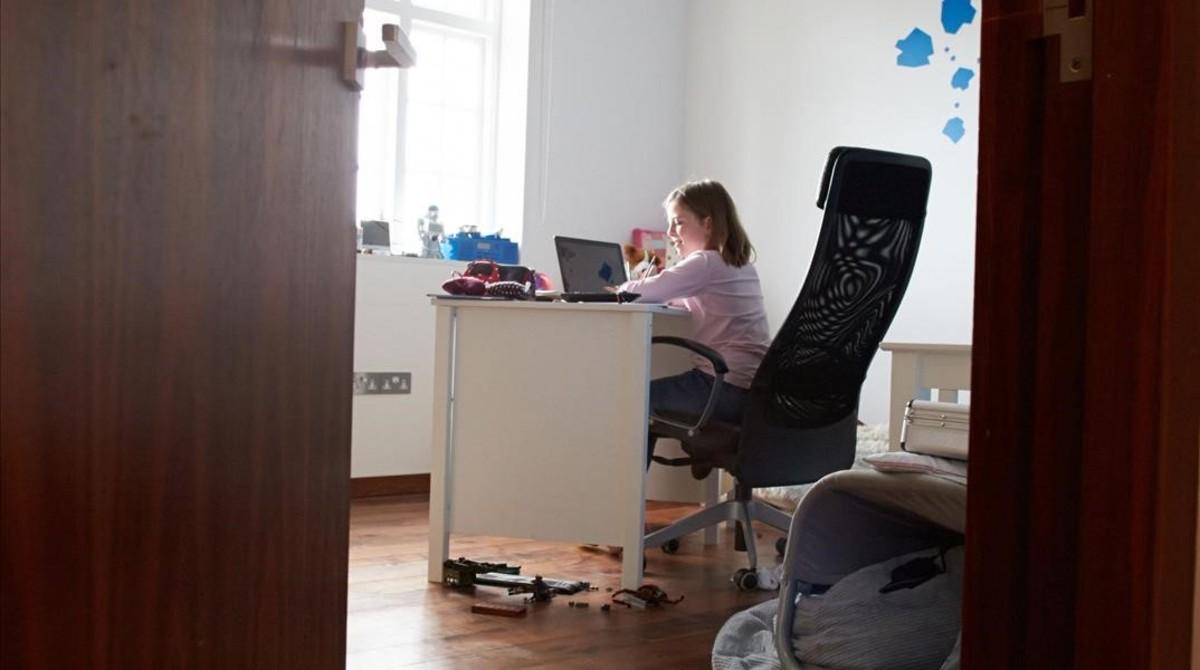 Una niña estudia en su habitación con el ordenador portátil.