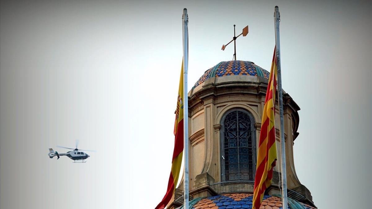 Un helicóptero sobrevula el Palau de la Generalitat, aún con las dos banderas.