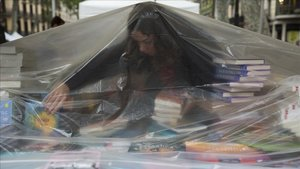 Una librera se protege de la lluvia caída a primera hora en Barcelona.