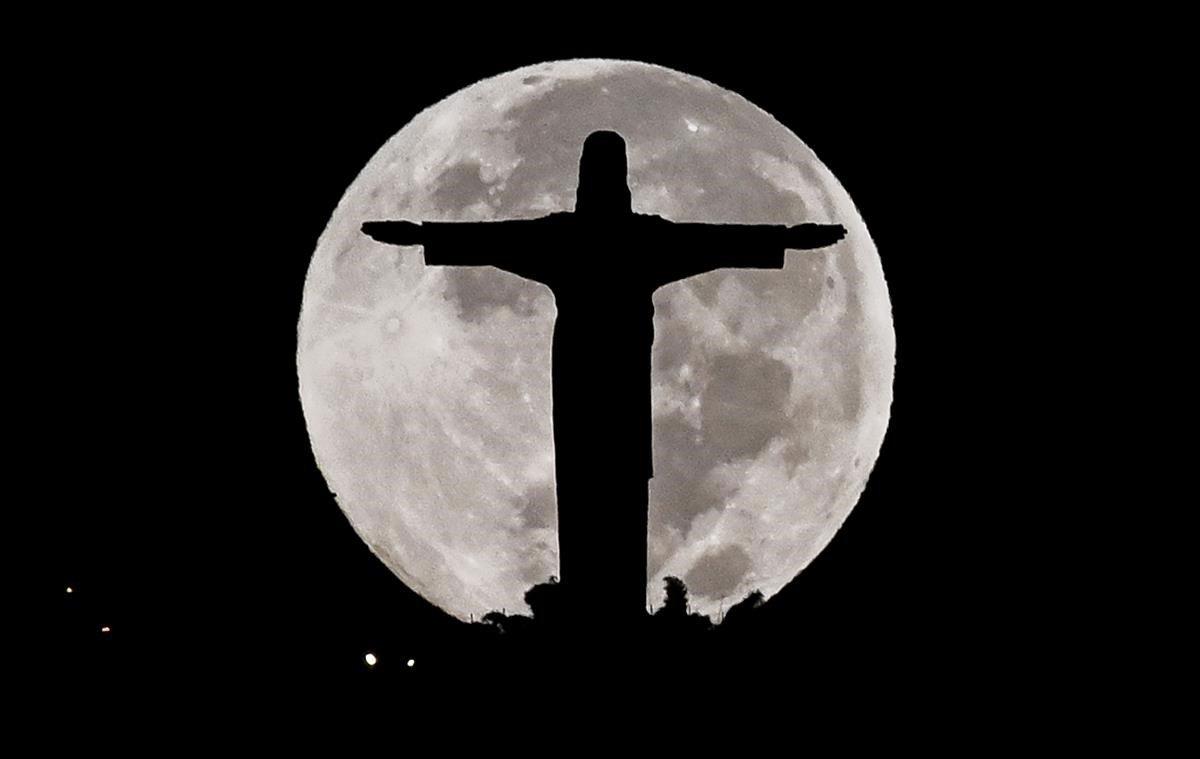 El monumento a Cristo Rey se recorta contra la luna llena en Cali, Colombia.