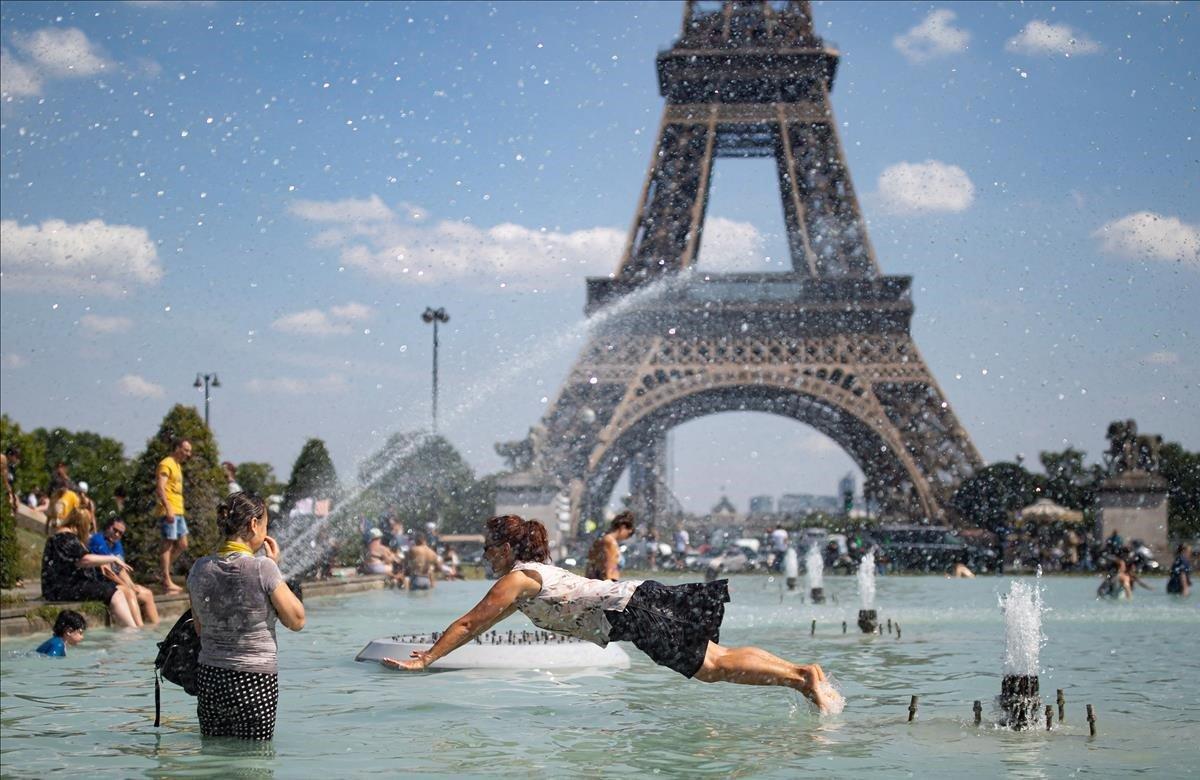 Una mujer se refresca con el agua de la fuente de la Plaza del Trocadero, frente a la Torre Eiffel, durante la ola de calor que recorre París este martes (Francia). Las temperaturas llegarán a los 40 grados centígrados esta semana.