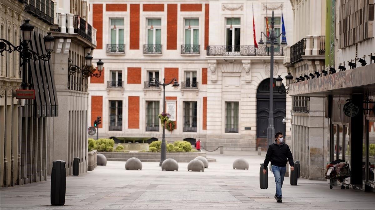 Un hombre camina por la Calle Preciados de Madrid, completamente vacía durante el confinamiento