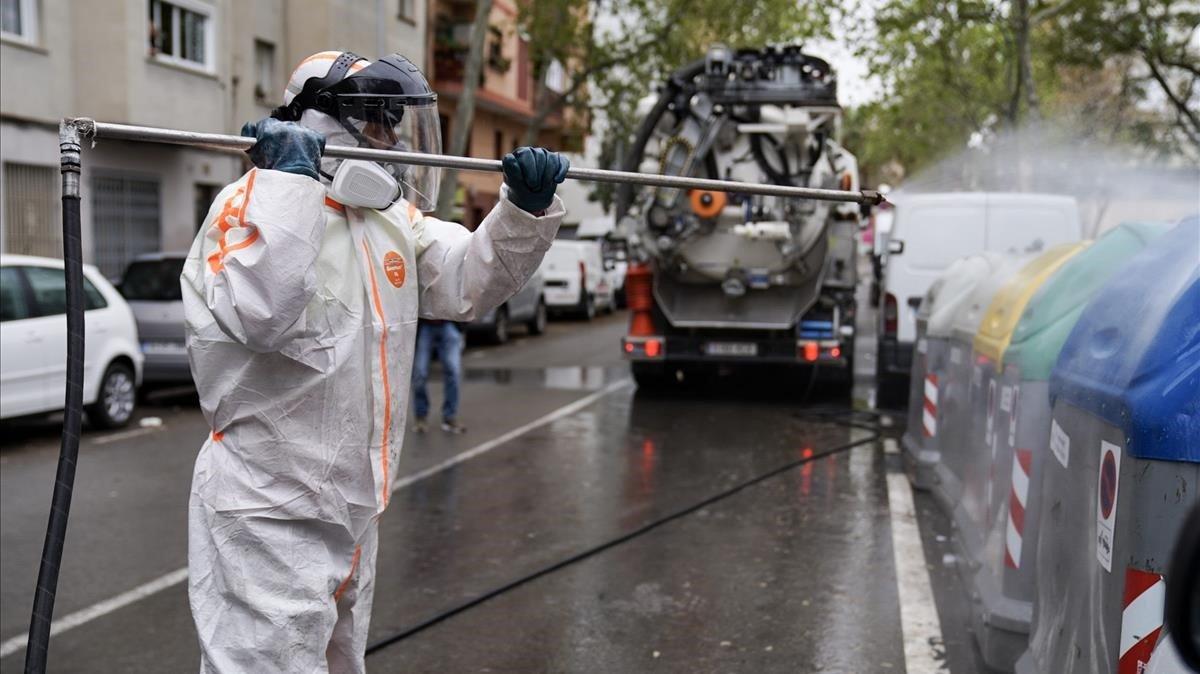 Un operario municipal desinfecta unos contenedores con una manguera a presión