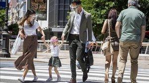 Una pareja pasea con su hija por una calle de València, todos con pantallas protectoras.