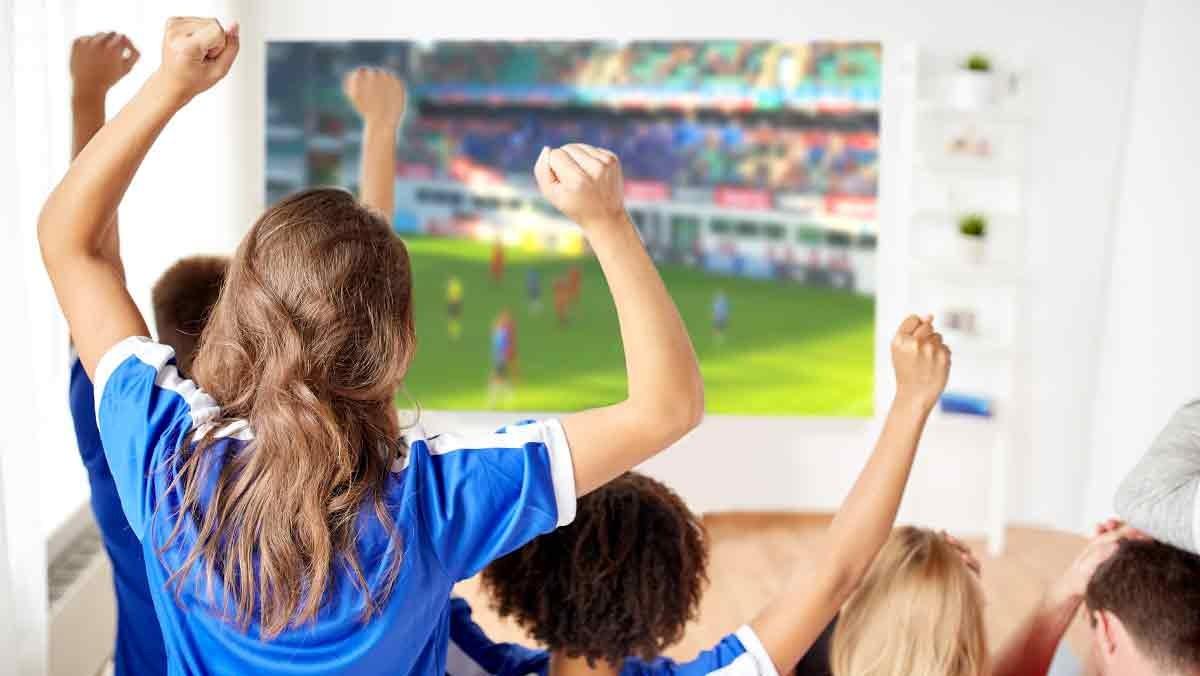 Aficionados viendo un partido de fútbol por televisión