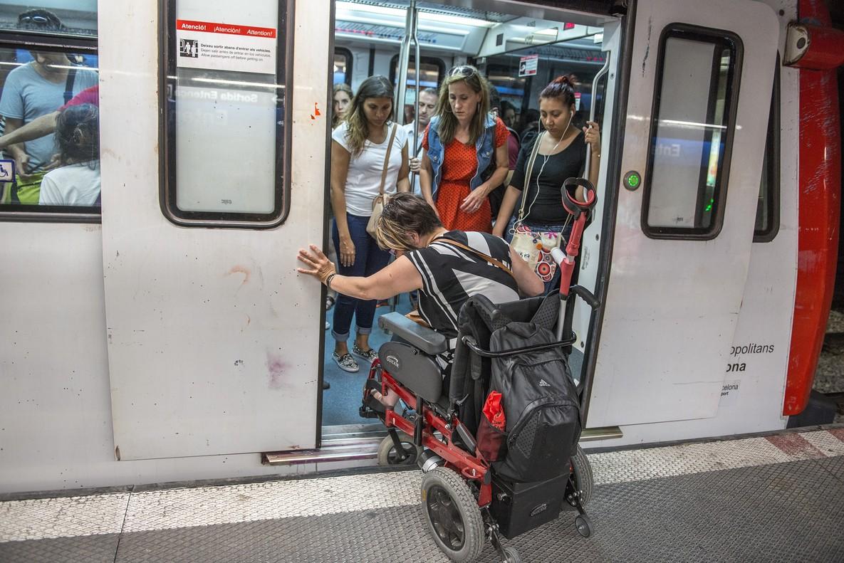 Una mujer en silla de ruedas intenta acceder al vagón del metro.