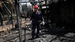 Un bombero inspecciona una de las viviendas quemadas por las llamas en la ciudad de Mati, próxima a Atenas.