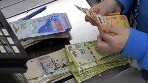 Un cajero cuenta billetes de pesos en un supermercado de Buenos Aires, el pasado jueves.