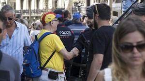 Un ciudadano saluda y felicita a los Mossos por su actuación durante los atentados. MIREIA REYNAL