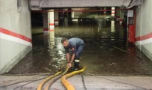 Un bombero trabaja en un garaje de la calle de Sant Pau de Barcelona.