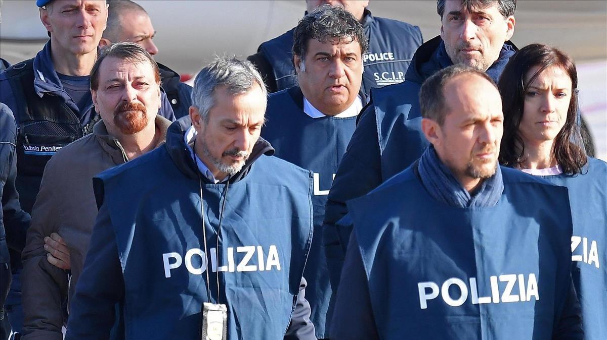 Cesare Battisti, izquierda, a su llegada al aeropuerto de Roma escoltado por varios policías.