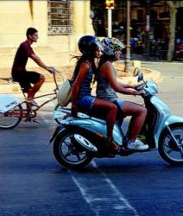Dos jóvenes circulan en un ciclomotor por Barcelona.