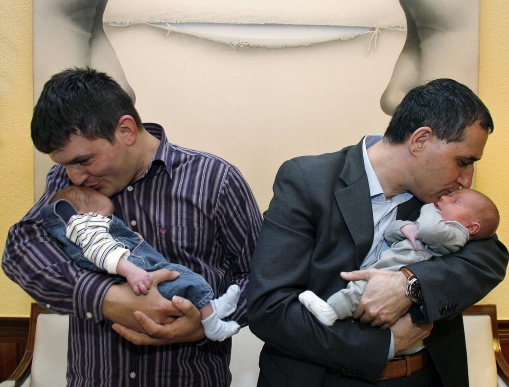 Dos padres acunan a sus bebés.