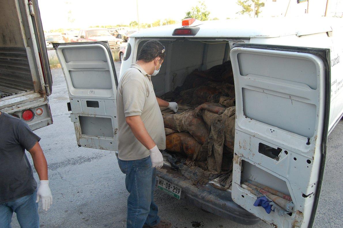 Peritos forenses descargan uno de los cadáveres hallados en las fosas clandestinas encontradas en Veracruz.