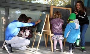 Dos alumnos de 5º y 6º de primaria juegan con tres niños de la guardería en la escuela de Rellinars.